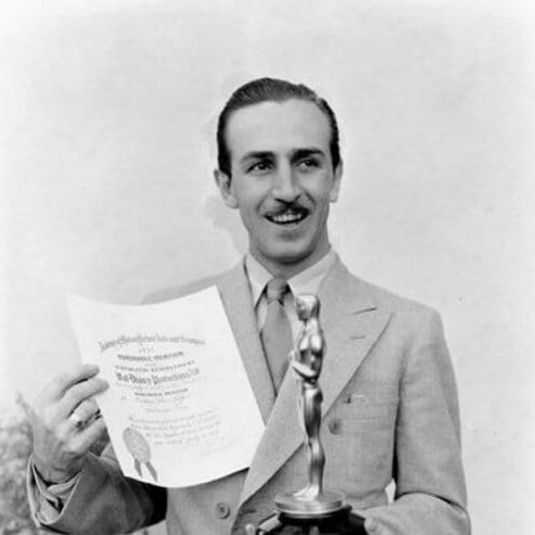Walt Disney poses with his first oscar, mid 1930s mens hairstyles