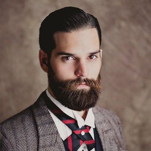 bearded man in suit - beard styles with hard part and slick hair