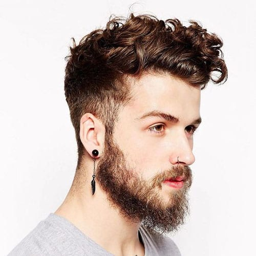 man with wavy beard and hair and a piercing