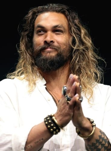jason momoa with long hair and blonde tips clapping and smiling